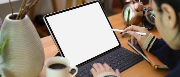 Freiberuflerin zeichnung auf tablette auf home-office-schreibtisch mit kaffeetasse und dekorationen Premium Fotos