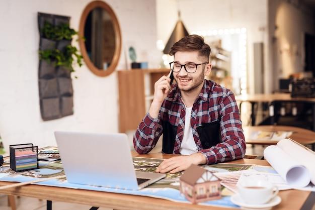 Freiberuflermann, der am telefon am laptop sitzt am schreibtisch spricht. Premium Fotos