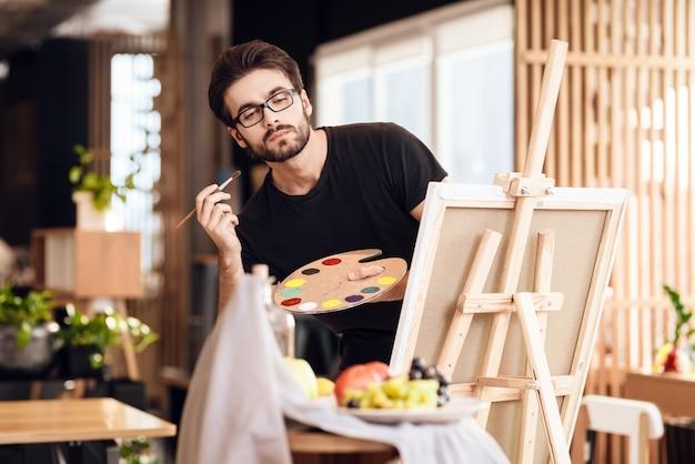 Freiberuflermannmalerei mit der bürste, die hinter gestell steht. Premium Fotos