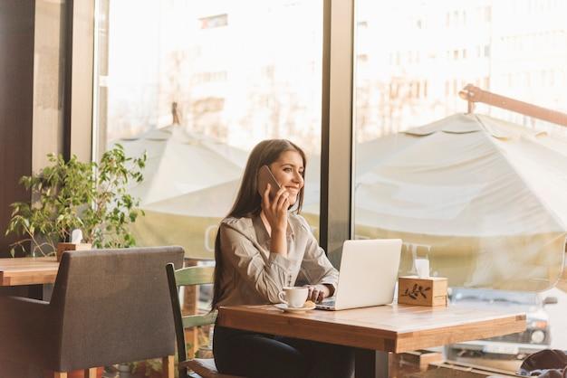 Freiberuflich tätige frau, die mit laptop in der kaffeestube arbeitet Kostenlose Fotos