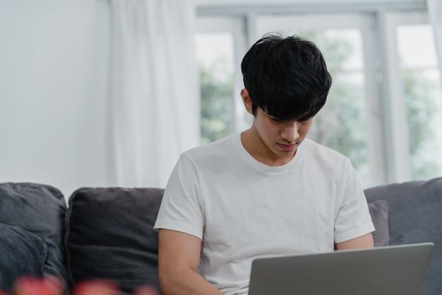Freiberuflich tätiger asiatischer mann, der zu hause, mann kreativ auf laptop auf sofa im wohnzimmer arbeitet. inhaberunternehmer des jungen mannes des geschäfts, spielcomputer, social media an arbeitsplatz am modernen haus überprüfend. Kostenlose Fotos