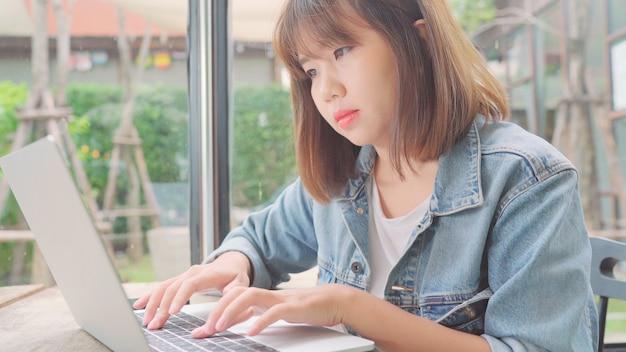 Freiberufliche asiatin des geschäfts, die arbeitet, projekte tut und e-mail auf laptop oder computer beim sitzen auf tabelle im café sendet. Kostenlose Fotos