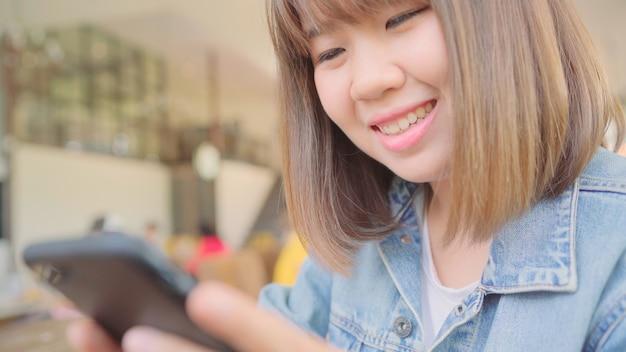Freiberufliche asiatin des geschäfts, die smartphone für das sprechen, lesen und simsen beim sitzen auf tabelle im café verwendet. intelligente schönheiten des lebensstils, die an den kaffeestubekonzepten arbeiten. Kostenlose Fotos