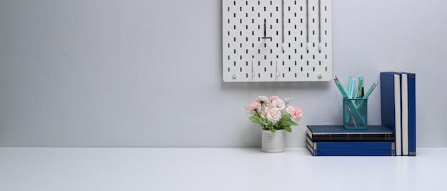 Freiberuflicher arbeitsplatz mit büchern, schreibwaren, blumentopf und kopierraum auf weißem tisch Premium Fotos