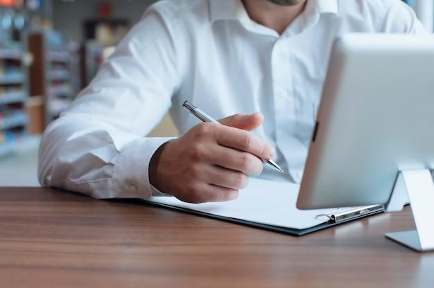 Freiberuflicher geschäftsmann in einem weißen hemd mit einem stift in den händen unterschreibt einen vertrag in einem café Premium Fotos