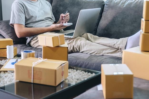 Freiberuflicher mann des jungen unternehmers kmu, der mit anmerkungsverpackungsartkasten-anlieferungsonline-markt auf bestellung arbeitet Premium Fotos