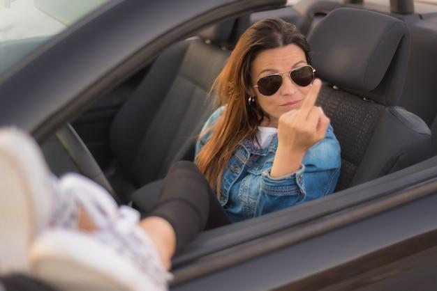 Freie frau, die den mittelfinger genießt ihr kabriolett zeigt. freiheit frau konzept. Premium Fotos