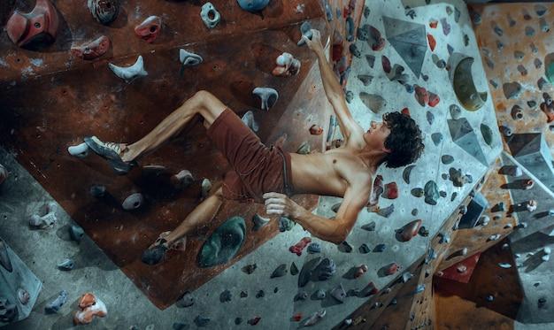 Freier kletterer junger mann, der künstlichen felsbrocken drinnen klettert. Kostenlose Fotos