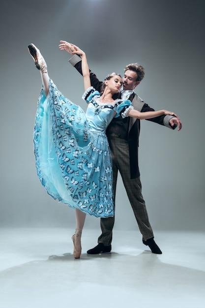 Freiflug. schöne zeitgenössische gesellschaftstänzer lokalisiert auf grauer wand. sinnliche professionelle künstler tanzen walz, tango, slowfox und quickstep. flexibel und schwerelos. Kostenlose Fotos