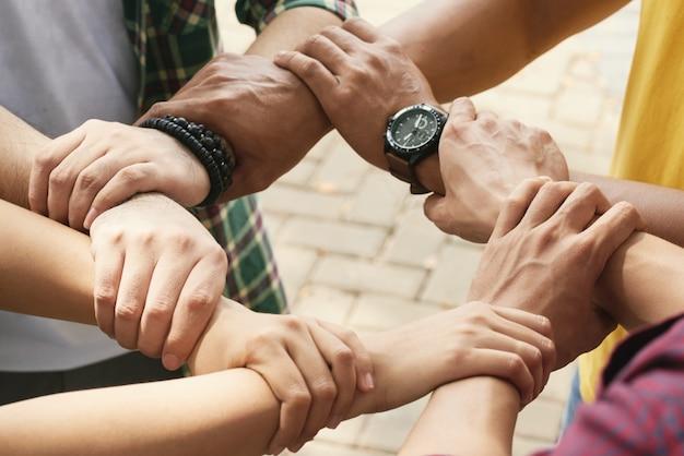 Freigestellte freunde, die handgelenke eines jeden in kette halten, um zu unterstützen und zusammenzuarbeiten Kostenlose Fotos