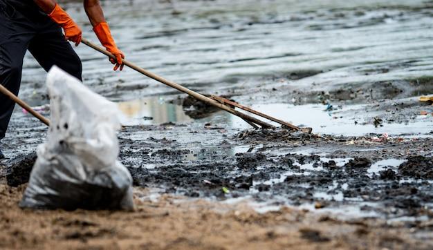 Freiwillige benutzen den rechen, um den müll aus dem meer zu kehren. strandreiniger müll sammeln Premium Fotos