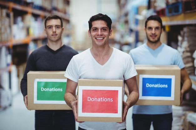 Freiwillige, die an der kamera hält spendenkästen in einem großen lager lächeln Premium Fotos