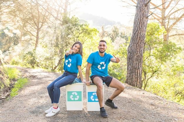 Freiwillige, die auf mülltonnen im holz sitzen Kostenlose Fotos