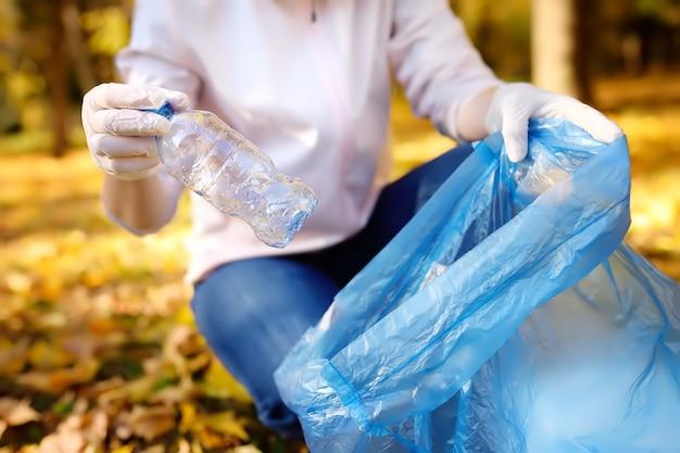 Freiwillige, die den müll einsammelt und im freien in einen biologisch abbaubaren müllsack wirft. Premium Fotos