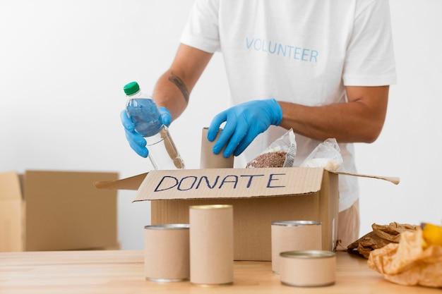 Freiwillige, die verschiedene goodies in spendenboxen legen Kostenlose Fotos