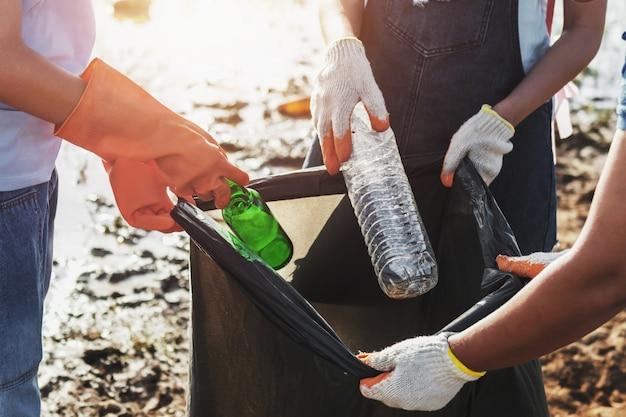 Freiwillige frau, die abfallplastik für das säubern am flusspark aufhebt Premium Fotos