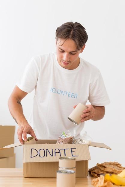 Freiwillige stellen dosen mit lebensmitteln in kisten Kostenlose Fotos
