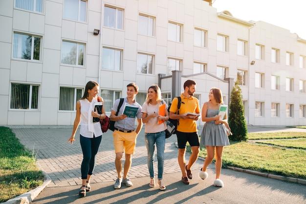 Freizeit eines studenten, campus-lebensrhythmus des junggesellen. fünf freundliche studenten gehen spazieren Kostenlose Fotos