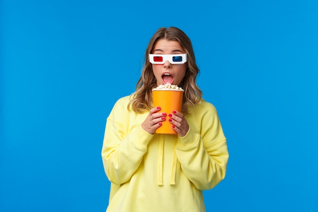 Freizeit-, spaß- und jugendkonzept. fröhliche hübsche blonde junge frau im gelben kapuzenpulli, der popcorn isst, schauen weg und tragen 3d brille als film im kino, Premium Fotos