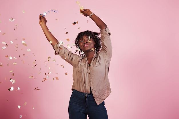 Freudig und glücklich. das konfetti in die luft werfen. afroamerikanerfrau mit rosa hintergrund dahinter Kostenlose Fotos