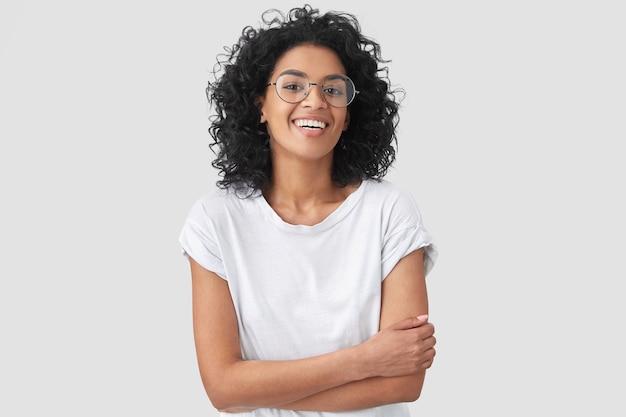 Freudige afroamerikanerin drückt die daumen, lacht über gute witze, trägt freizeitkleidung und runde brillen, isoliert. glückliche junge frau mit dunkler haut wirft innen auf Kostenlose Fotos