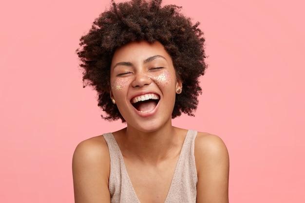 Freudige afroamerikanerin mit dunkler haut, lacht glücklich, öffnet den mund weit, funkelt auf den wangen, schließt die augen, hat lockiges haar, isoliert über der rosa wand. menschen- und glückskonzept Kostenlose Fotos