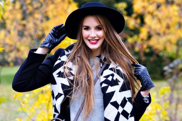 Freudige dame im schwarzen hut und in den handschuhen, die mit langen haaren mit wald auf hintergrund spielen. schönes mädchen, das mantel und stilvollen schal trägt, der während des spaziergangs im herbstpark lächelt. Kostenlose Fotos