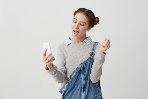Freudige frau in lässigen overalls mit handy für die interaktion über kopfhörer. fashion weibliche blogger facetime mit ihrem freund beim ausruhen im café. beziehungskonzept Kostenlose Fotos