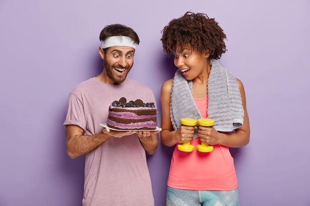 Freudige frauen und männer starren mit glück und versuchung auf köstlichen kuchen, sind nach erschöpftem training hungrig, vermeiden es, süße desserts mit viel kalorien zu essen, trainieren sie mit hanteln im fitnessstudio Kostenlose Fotos