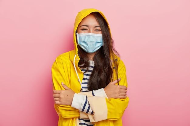 Freudige hübsche frau mit schwarzen haaren, verschränkten armen, medizinischer maske, schützt sich vor saisonalen krankheiten und trägt einen wasserdichten regenmantel Kostenlose Fotos