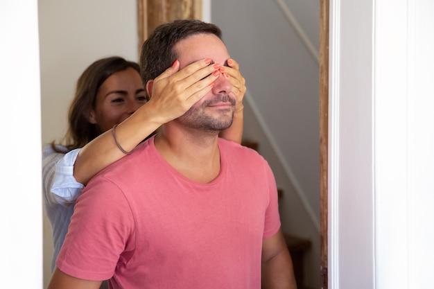 Freudige junge frau, die die augen seines freundes mit den händen bedeckt und ihn in ihre neue wohnung führt Kostenlose Fotos