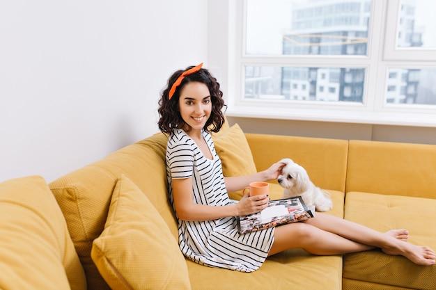 Freudige junge frau mit geschnittenem brünettem haar im kleid, das mit hund auf couch in der modernen wohnung kühlt. lesemagazin, tasse tee, komfort, gemütliche zeit zu hause mit haustieren Kostenlose Fotos