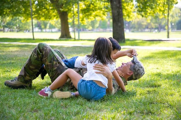 Freudige kinder und ihr vater liegen und spielen auf gras im park. glückliches militärisches vatertreffen mit kindern nach missionsreise. familientreffen oder rückkehr nach hause konzept Kostenlose Fotos