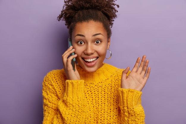 Freudige lockige junge frau spricht am telefon, freut sich über gute nachrichten, gesten während des gesprächs, hebt die handfläche, trägt ohrringe und gelben pullover, genießt gelegenheitsgespräche, isoliert über lila hintergrund Kostenlose Fotos
