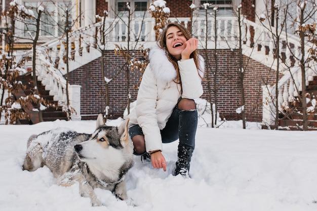 Freudige modische junge frau, die spaß mit husky-hund im schnee auf straße im freien hat. lieben sie haustiere, schöne momente, lächeln sie, drücken sie wahre positive gefühle aus. Kostenlose Fotos