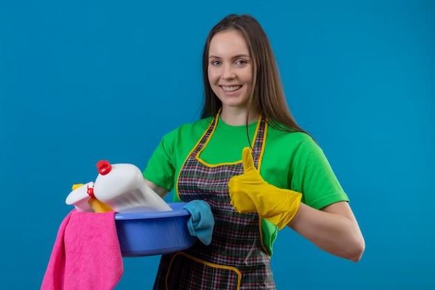 Freudige reinigung der jungen frau, die uniform in handschuhen hält, die reinigungswerkzeuge auf isolierter blauer wand halten Kostenlose Fotos