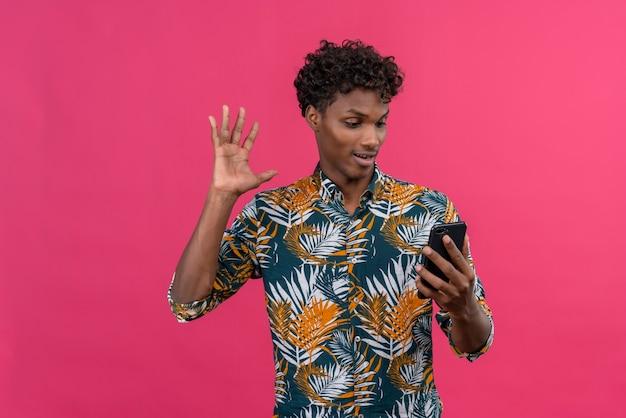 Freudiger gut aussehender dunkelhäutiger mann mit lockigem haar im bedruckten hemd der blätter, das mit freund während des videoanrufs spricht und hand auf frontkamera des mobiltelefons auf einem rosa hintergrund winkt Kostenlose Fotos