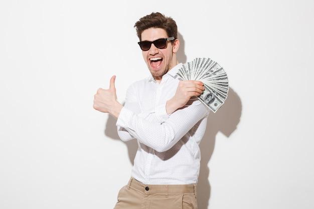 Freudiger mann im hemd und in der sonnenbrille, die sich freuen, während sie fan des geldes in der dollarwährung demonstrieren und daumen oben zeigen, lokalisiert über weißer wand mit schatten Premium Fotos