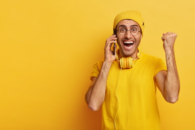 Freudiger optimistischer mann mit zahnigem lächeln, erhebt triumphierend die geballte faust, ruft per smartphone an, genießt unterhaltung Kostenlose Fotos