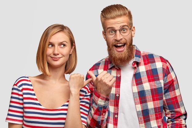 Freudiges glückliches junges paar haben spaß zusammen, zeigen sich an, haben glückliche ausdrücke, stehen gegen weiße wand Kostenlose Fotos