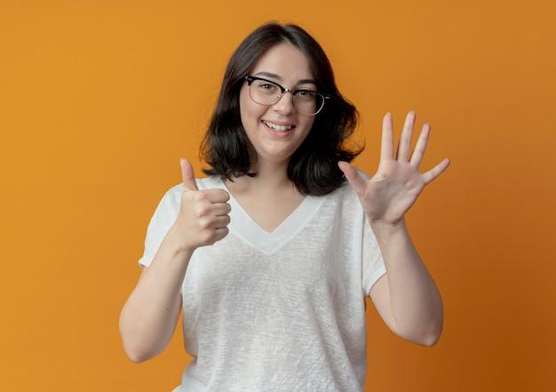 Freudiges junges hübsches kaukasisches mädchen, das brillen trägt, die sechs mit den händen lokalisiert auf orange hintergrund zeigen Kostenlose Fotos