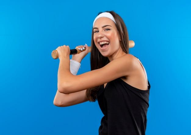 Freudiges junges hübsches sportliches mädchen, das stirnband und armband hält baseballschläger lokalisiert auf blauem raum trägt Kostenlose Fotos