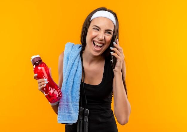 Freudiges junges hübsches sportliches mädchen, das stirnband und armband hält wasserflasche hält, die am telefon spricht, das seite betrachtet Kostenlose Fotos