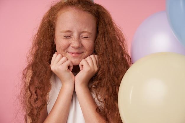 Freudiges weibliches kind mit foxy langen haaren in festlichen kleidern, die über rosa hintergrund mit geschlossenen augen aufwerfen, drückt wahre positive gefühle aus und hält hände unter kinn. kinder- und feierkonzept Kostenlose Fotos