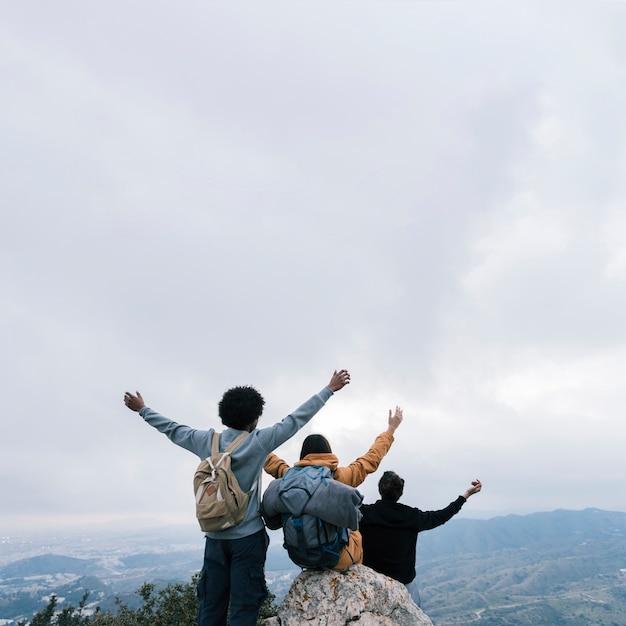 Freunde auf der oberseite des berges ihre arme gegen weißen bewölkten himmel anhebend Kostenlose Fotos