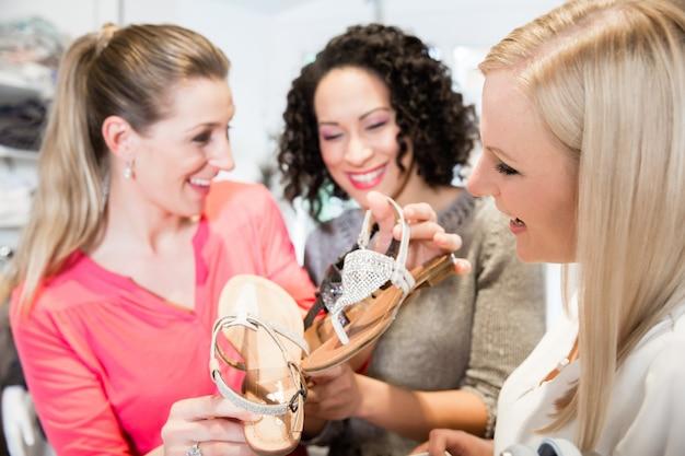 Freunde auf einem einkaufsbummel diskutieren sandalen und schuhe kaufen Premium Fotos