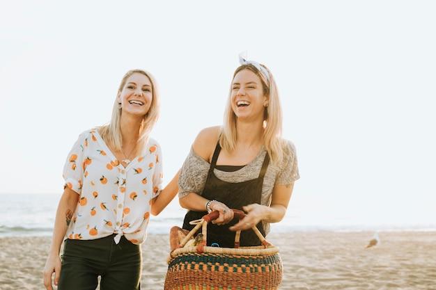 Freunde, die am strand mit einem picknickkorb gehen Premium Fotos