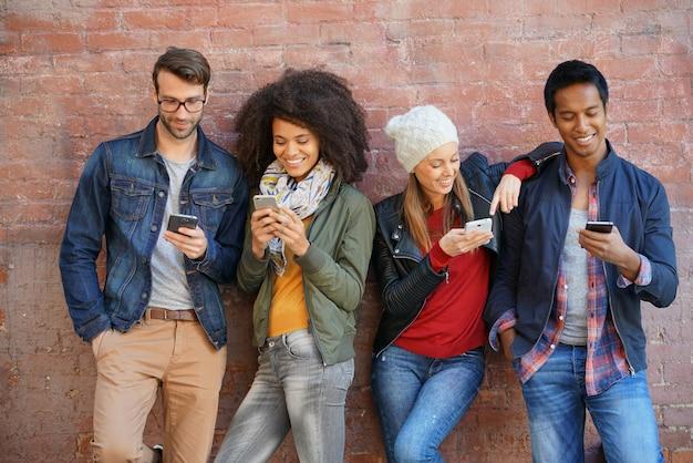 Freunde, die auf backsteinmauer, spielend mit smartphones sich lehnen Premium Fotos