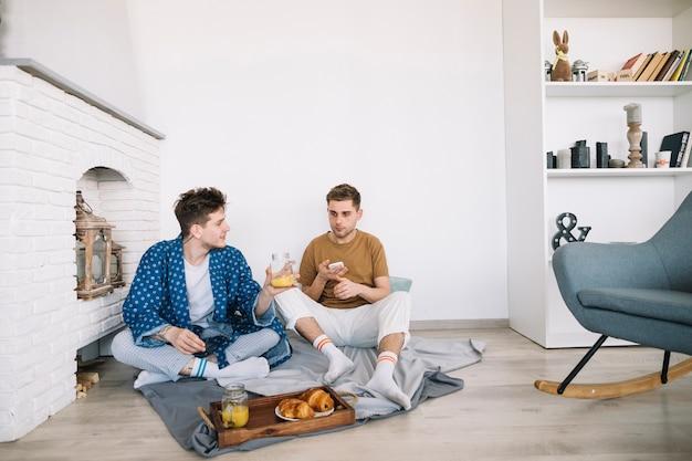 Freunde, die auf dem boden zu hause isst köstliches essen sitzen Kostenlose Fotos