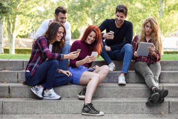 Freunde, die auf ein paar Schritte mit Smartphones und Tablets sitzen Kostenlose Fotos